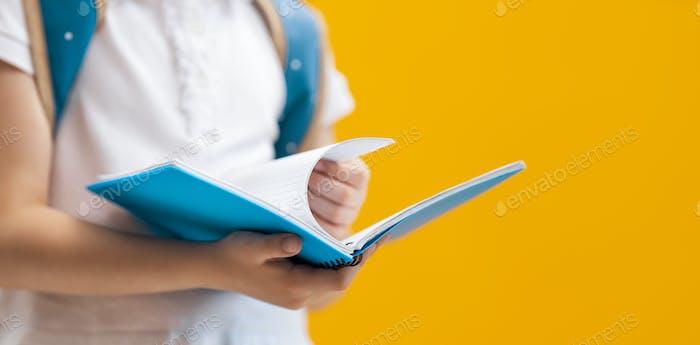 Kind mit Buch auf dem Hintergrund der gelben Wand.