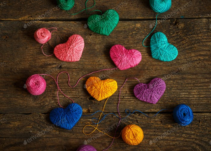 Multicolored Hearts with a balls of thread on old shabby wooden