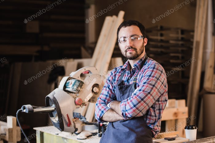 Happy young handyman carpenter in workshop, smiling