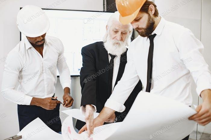 Gruppe von Managern im Büro mit Helm