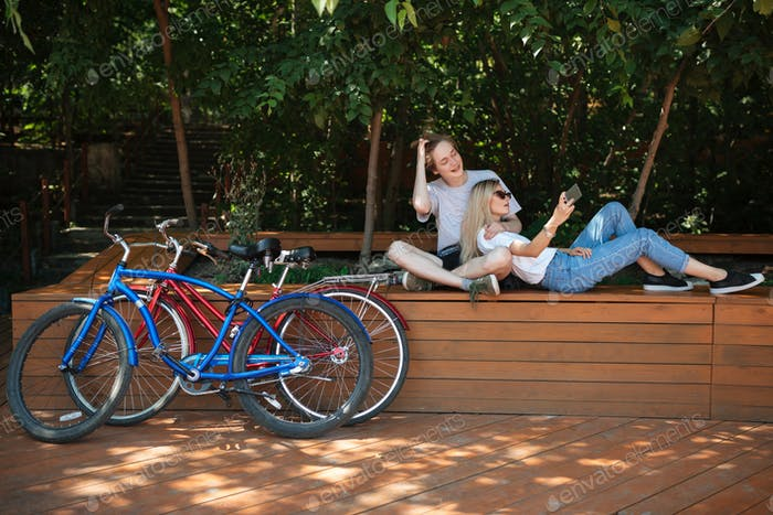 Young couple spending time in park with red and blue bicycles nearby