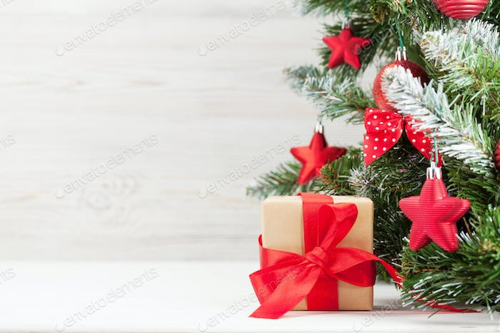 Christmas card with decorated fir tree and gift