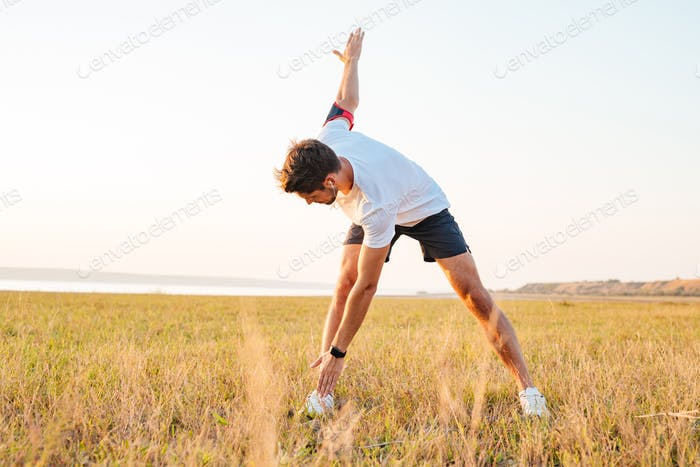 Young sportsman standing and stretching in the morning