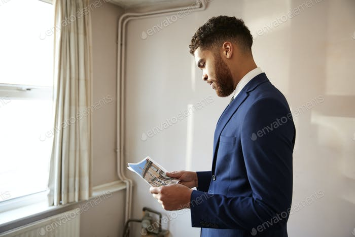 Male Realtor Looking At House Details In Property For Renovation