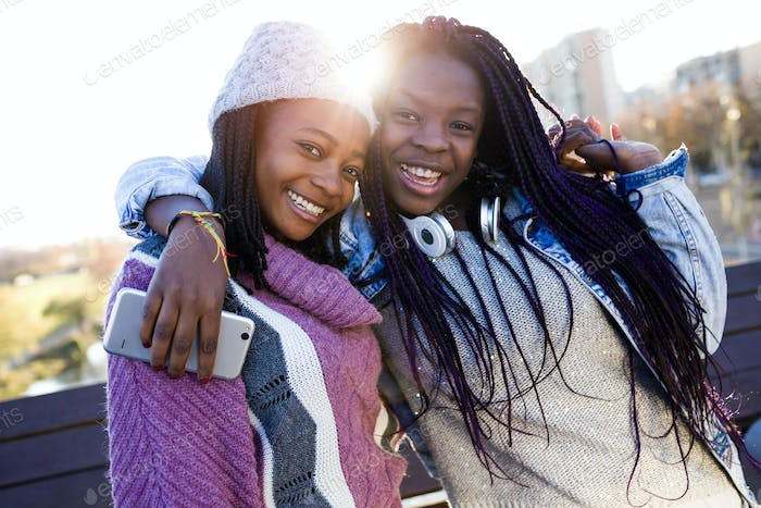 Two beautiful young woman looking at camera in the street.