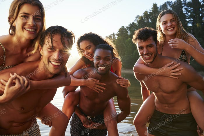 Three young adult couples piggy backing in a lake, close up