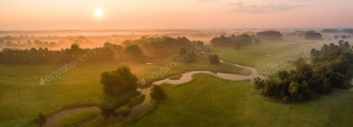 Sunrise over riparian forest with tortuous river meanders in summer