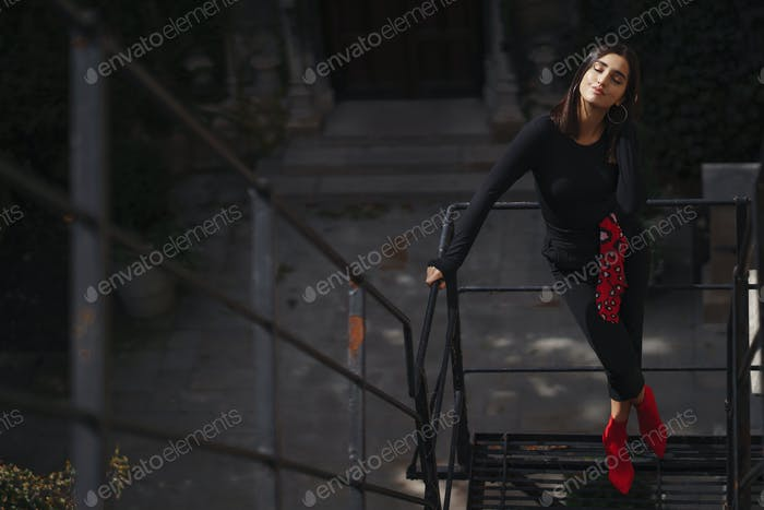 hermosa morena posando en un negro escalera