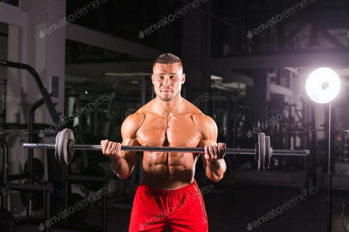 Powerful bodybuilder doing the exercises with barbell