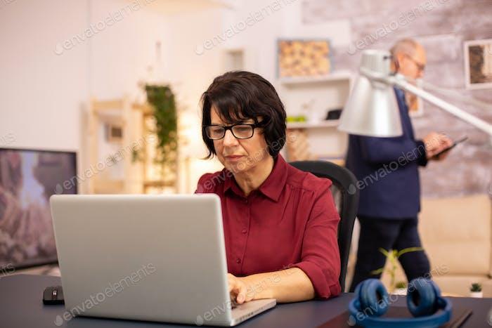 Alte Frau mit einem modernen Computer in ihrem Wohnzimmer