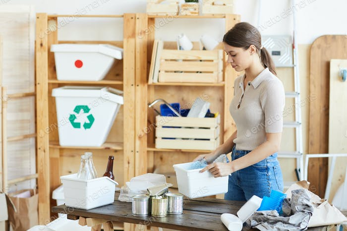 Woman sorting garbage in boxes