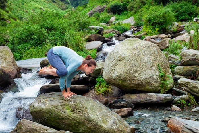 Woman doing Kakasana asana arm balance outdoors