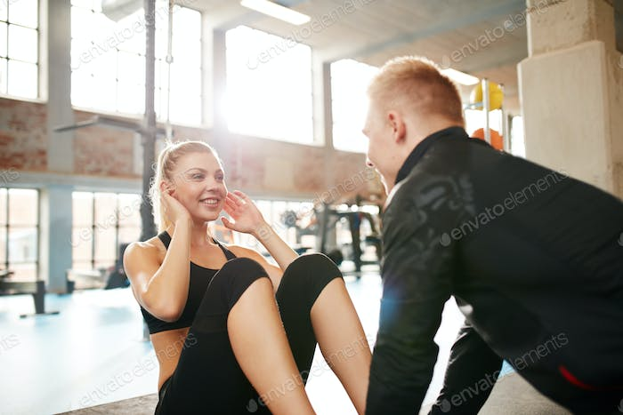 Young woman doing sit-ups with her personal trainer