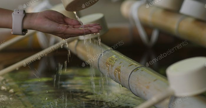 Woman wash hand before enter Japanese temple