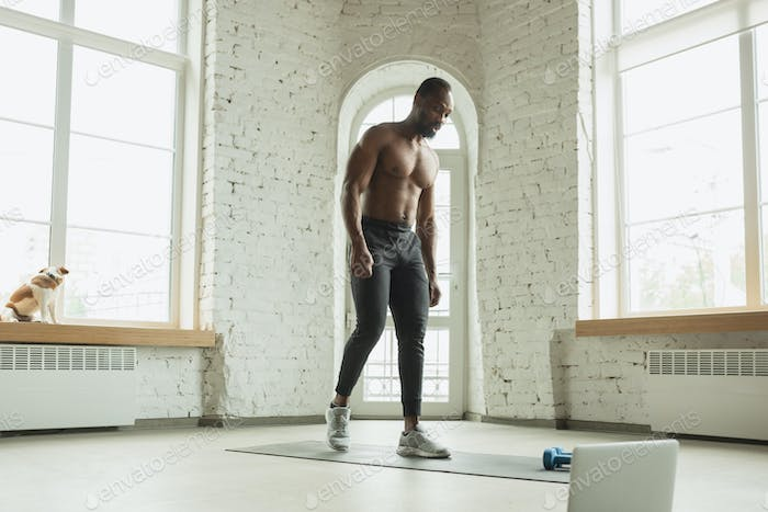 Young african-american man training at home during quarantine of coronavirus outbreak, doinc