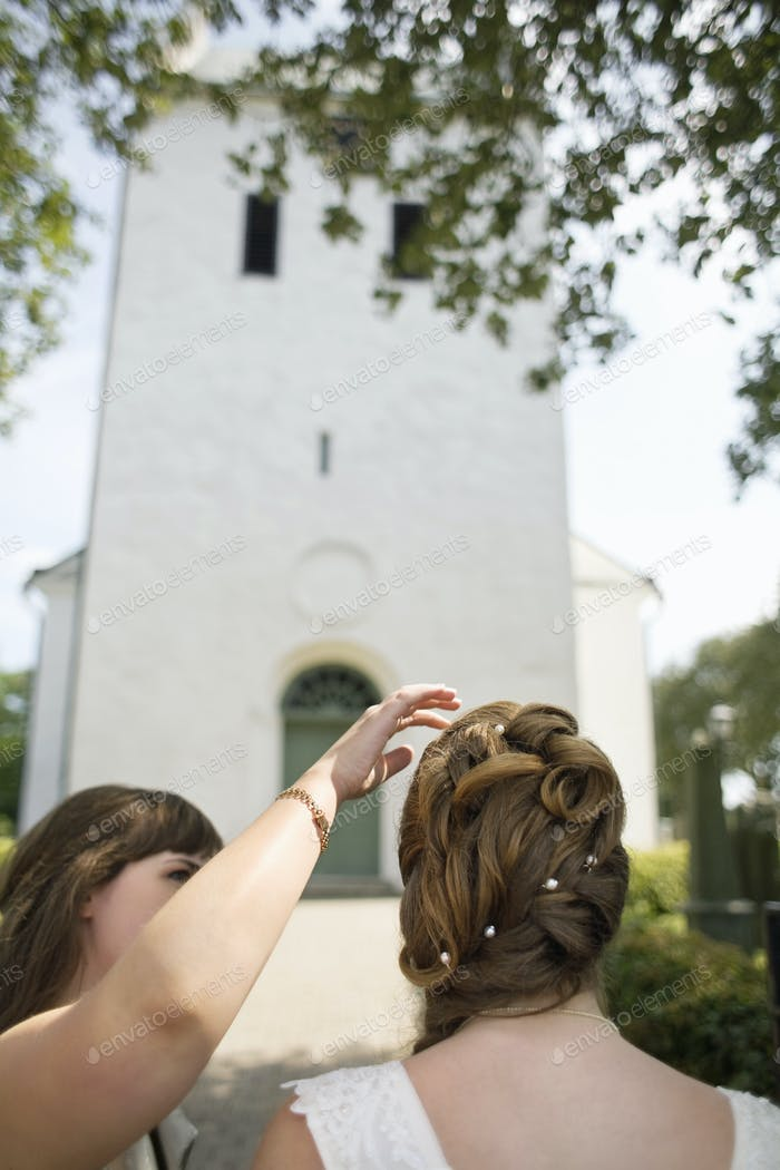 Close-up of maid assisting bride outside church
