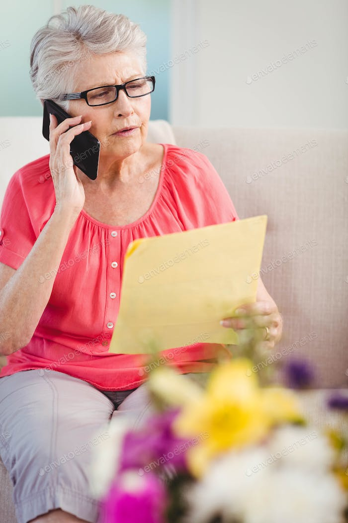 Senior woman reading a letter and talking on phone in living room