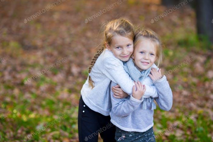 Kleine entzückende Schwestern bei warmen sonnigen Herbsttag im freien