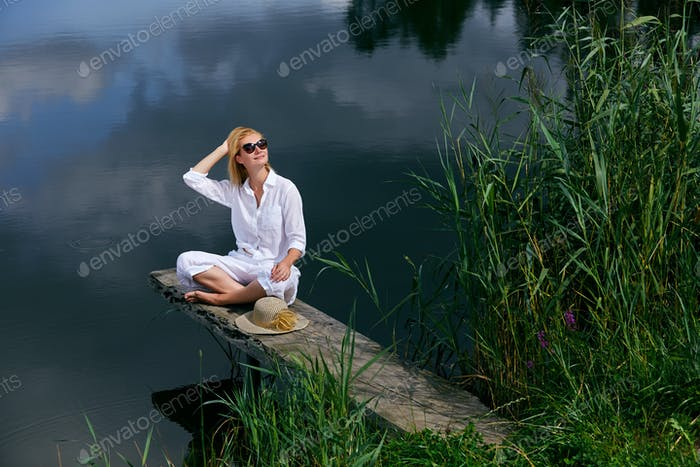 Young woman resting near lake