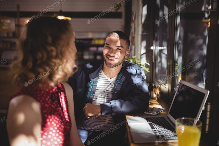 Smiling young man talking with female friend sitting at coffee shop
