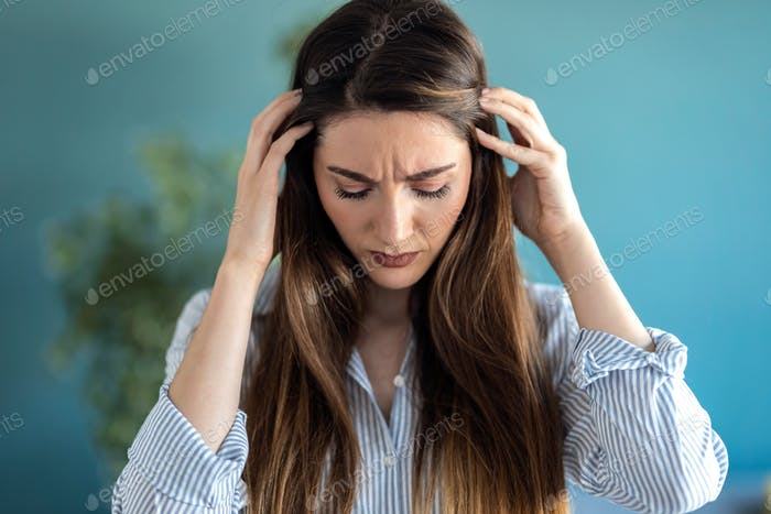 Frustrated young woman with headache and frowning while standing at home.