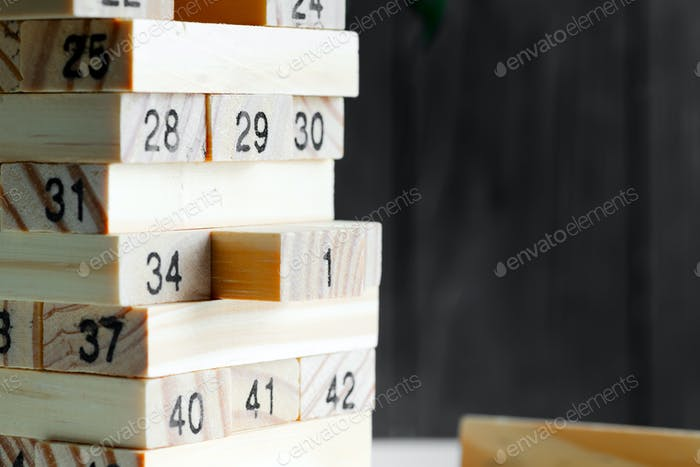 Wooden creative constructor from blocks with numbers against black background. Jenga game for