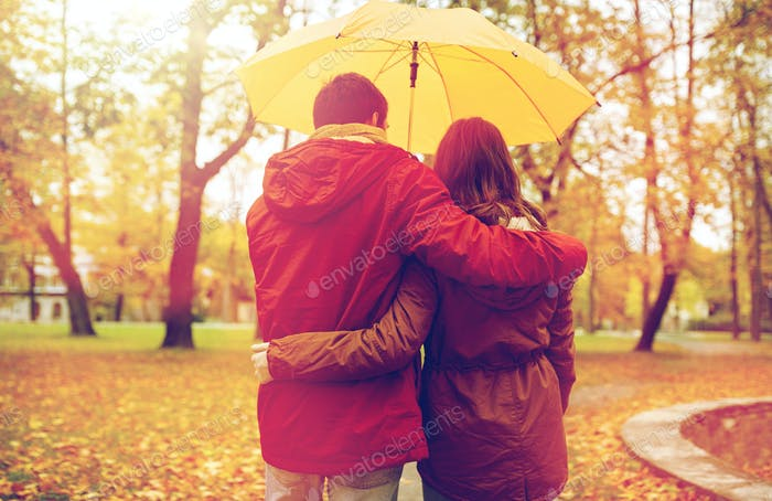 happy couple with umbrella walking in autumn park