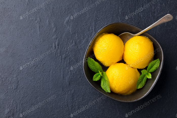 Mango Ice Cream, Tropical Fruit Sorbet in Black Bowl on Slate Background. Copy Space. Top View