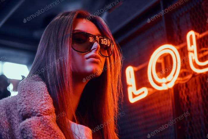 Portrait of a sensual young girl wearing sunglasses and coat