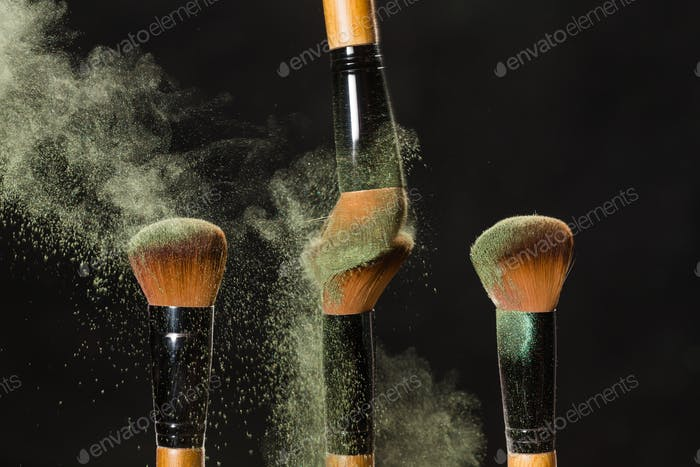 Mineral make up and objects concept - Four make up brushers in dust over dark background