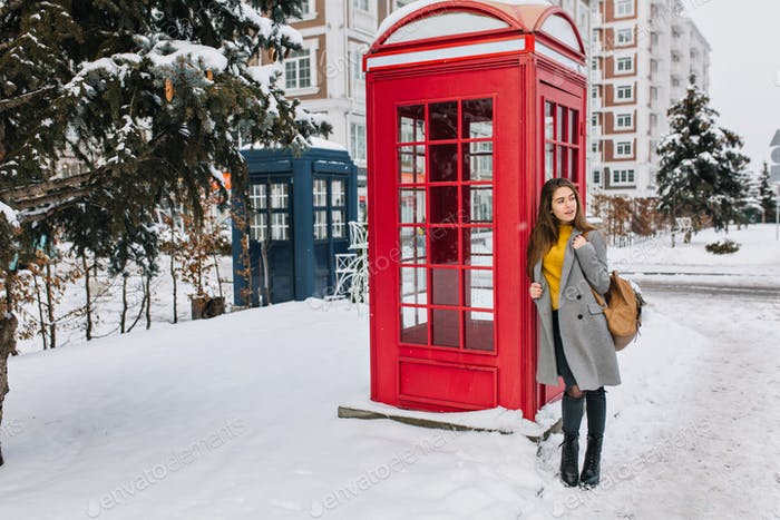Full-length portrait of lovely european lady with leather bag standing near phone booth and looking