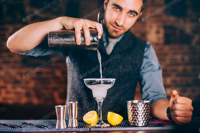 Portrait of handsome bartender using bar tools for alcoholic cocktails.