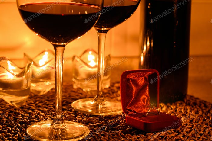 Romantic background with glasses of wine and ring