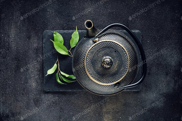 Green tea leaf with black teapot