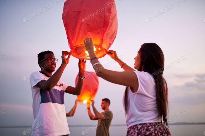 Smiling couple launching Chinese lanterns as symbol of love