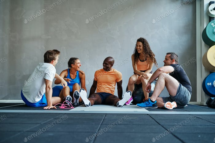 Diverse group of friends sitting in a gym talking together