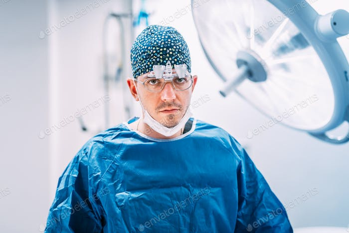 Close up portrait of plastic surgeon with surgical scrubs and lamps in operating room