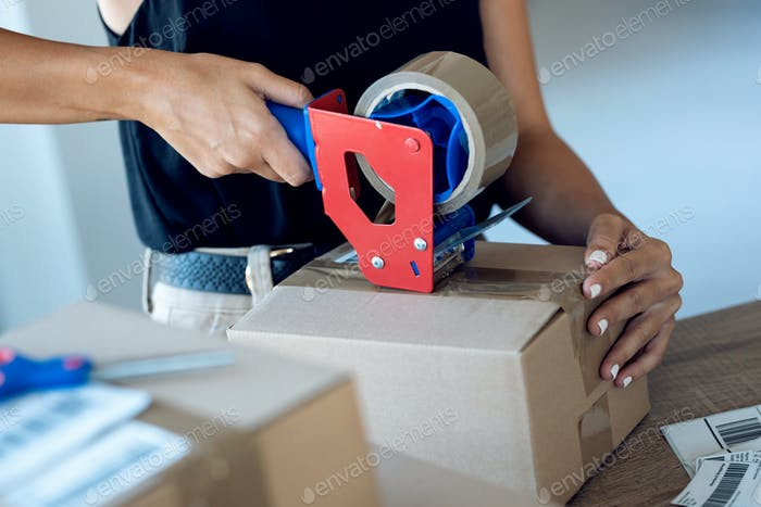 Nahaufnahme der Hände einer jungen Frau, die eine Verpackungsmaschine halten