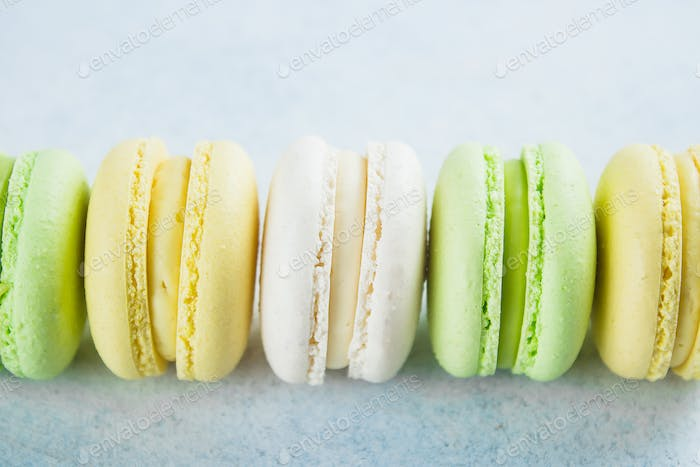 Cake macaron or macaroon on light blue background from above. Colorful almond cookies, pastel colors