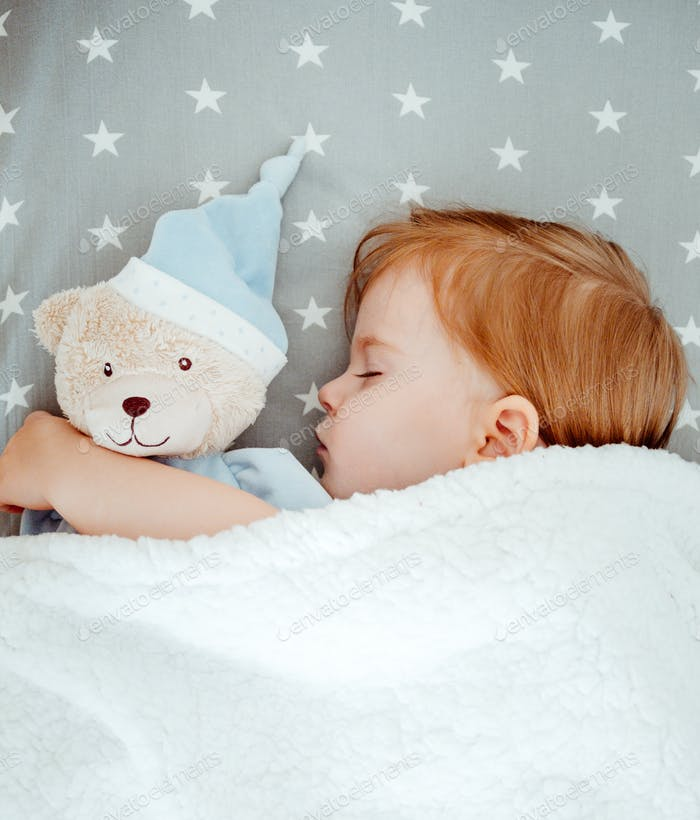Little baby girl sleeping with her bear toy.
