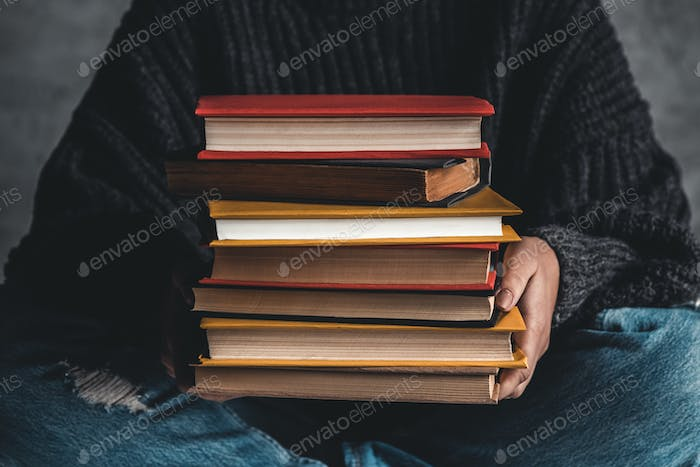 Student holding in hand a stack of old books