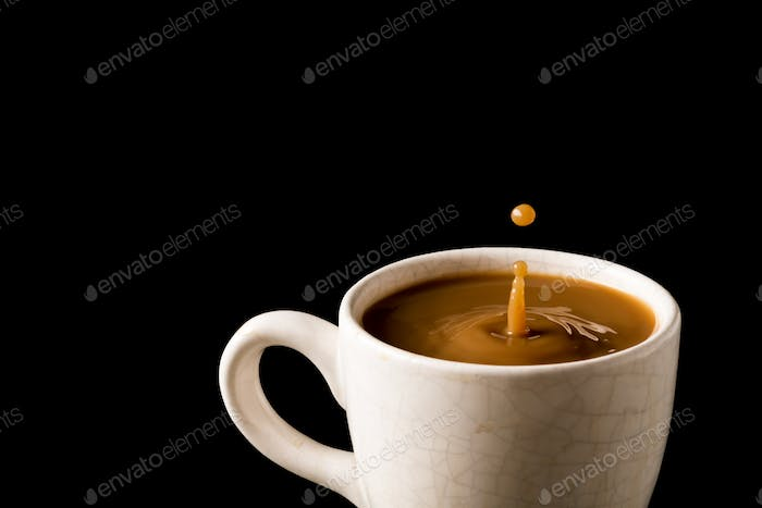 A cup of coffee with a drop on black background.