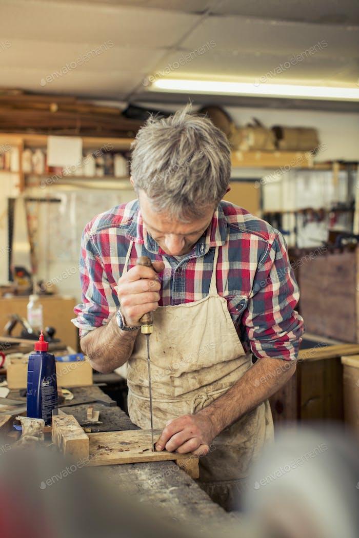 Ein antikes Möbelrestaurateur, das mit einem Handwerkzeug auf einer Werkbank arbeitet.