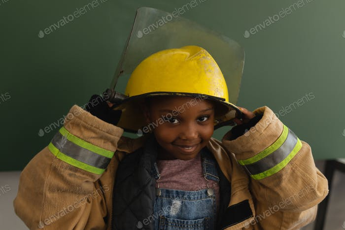 Schoolgirl with a too big fire uniform in classroom