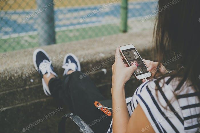 Junge Frau mit einem Smartphone im Park