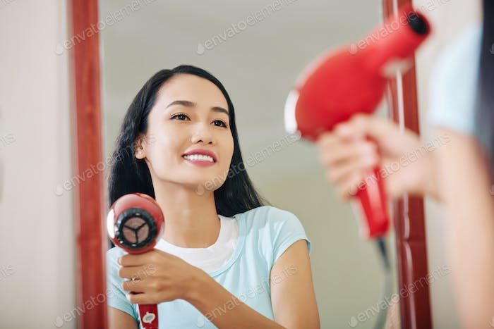 Smiling woman drying her hair