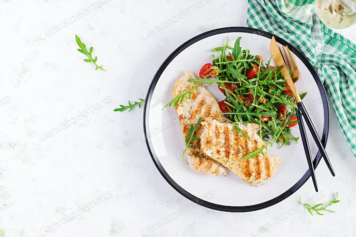 Grilled chicken fillet with fresh salad - arugula and tomato.