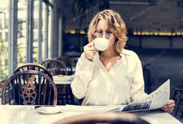 Business woman reading newspaper in the morning