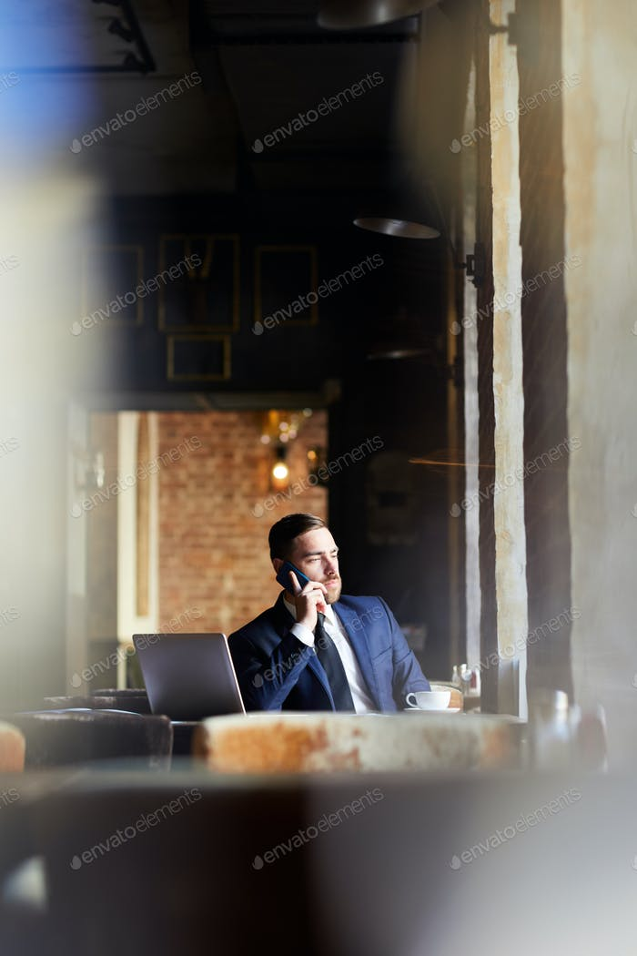 Confident business executive communicating on phone