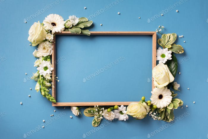 Frame of white flowers over blue background. Valentines day, Woman day concept. Spring or summer